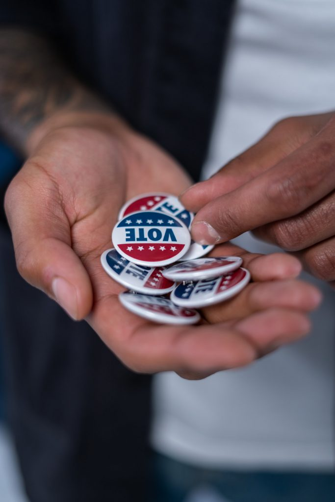 "picture of a man holding ""vote"" buttons with American flag theme"